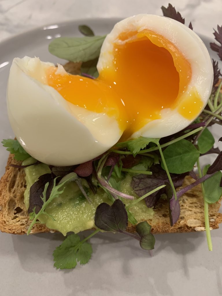 A piece of toast topped with avocado mash, micro greens and a soft boiled egg. The avocado toast is sitting on top of a gray plate.