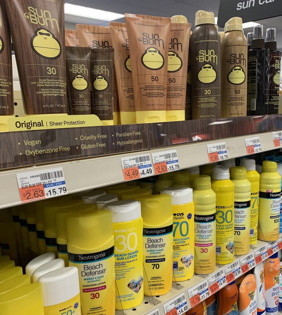 shelves of sunscreen bottles, tubes and sprays in a drug store