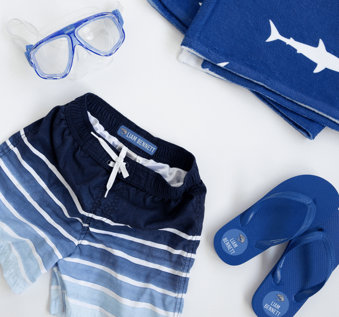 Blue Swim Shorts and blue flip flops featuring water proof name labels by Label Daddy