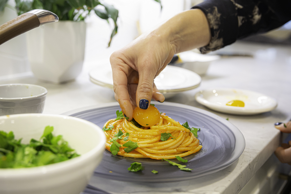 placing a cured egg yolk in the center of a bucatini pasta nest