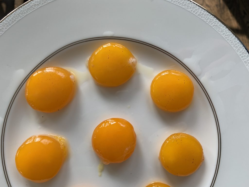 Eggs yolks that have been cured for 12 hours sitting on on white china