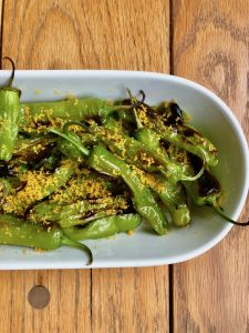 Green shishito peppers topped with grated yellow bottarga. Bottarga is a salted cured fish roe.