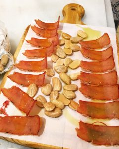Pieces of sliced bottarga and marcona nuts served on a white plate